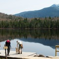 Hikers enjoying the dock at Lonesome Lake.- Lonesome Lake AMC Hut