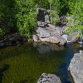 The trail leads to the overlook of the Fern Gully swimming hole. The clear water makes the water look shallower than it really is.- Fern Gully Swimming Hole