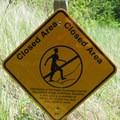 A caution sign warning to stay off dunes.- Red Trail
