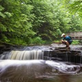A hiker taking some pictures of the flowing water.- Ricketts Glen State Park