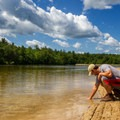 A hiker tests out the water at Sand Spring Lake.- Hickory Run State Park