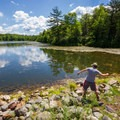 A hiker skipping stones on the far shores of Sand Spring Lake.- Hickory Run State Park