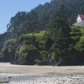View of the Heceta Head Lighthouse residence building from Cape Cove Beach.- Cape Cove Beach