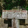 Trail sign beside the kiosk pointing the way.- Arethusa Falls