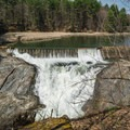Water flowing over the dam along the trail to Dewey's Mill Pond.- Quechee State Park