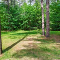 A smaller recreation field with a volleyball net.- Quechee State Park Campground