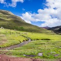 The trailhead is striking with bright green grass and alpacas dotting the horizon.- Vinicunca / Rainbow Mountain