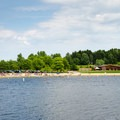 View of the beach and park building from across the lake.- Lake Taghkanic State Park