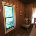 Ample natural light with views of the forest in the bedroom of Cabin 1.- Jawbone Flats