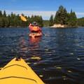 Kayakers paddling on beautiful Bennett Lake head toward a picturesque island.- Bennett Lake