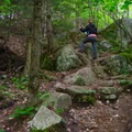 A hiker navigates the rocks on the trail.- Beer Walls in Chapel Pond Canyon