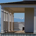 Olympic Mountains through the porch of the Officers' Quarters.- San Juan Island National Historical Park