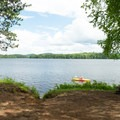 A paddler passes a campsite.- Fish Creek Pond Campground