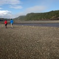 A couple strolls the rocky beach at low tide.- Point Wolfe Beach Trail