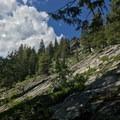 Large slabs of granite sit on the hillside.- Boulder Lake