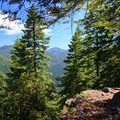 A break in the forest reveals mountainous views as the trail rounds a ridge.- Henline Mountain
