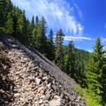 The trail crosses another scree field nearing the lookout site.- Henline Mountain