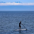 Paddleboarding with the Olympic Range in the distance at the Esquimalt Lagoon Migratory Bird Sanctuary.- Esquimalt Lagoon Migratory Bird Sanctuary