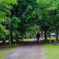 A camper riding a bike along the road.- Wilmington Notch Campground