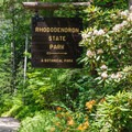 Entrance sign with colorful flowers.- Rhododendron State Park