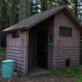 Single vault toilet across the driveway from the station.- Musick Guard Station