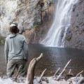 The base of Fairy Falls lands in a shallow, clear, blue pool.- Fairy Falls via Freight Road Trailhead
