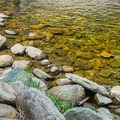 Crystal clear water at the rocky shoreline.- Buttermilk Falls Swimming Hole