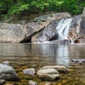 A swimmer sits in the middle falls.- Buttermilk Falls Swimming Hole