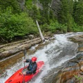 Sliding down Siyeh bedrock on one of the cleaner sections.- Siyeh Creek to St. Mary's Lake via Reynolds Creek