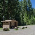 Vault toilets in the parking area for Skookum Creek Campground.- Otter Lake
