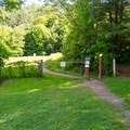 The trail from the parking lot leads to a grassy area, then the trailhead.- Vroman's Nose