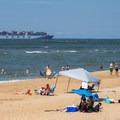 People sunbathing on the beach with a cargo ship in the distance.- First Landing State Park
