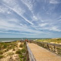 Boardwalk over the dunes from the main parking lot.- First Landing State Park