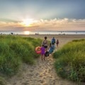 A family makes their way out for a swim during sunset.- First Landing State Park