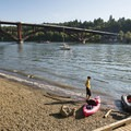 Sellwood Riverfront Park beach on the Willamette River with the 2016-opened Sellwood Bridge.- Sellwood Riverfront Park Beach