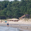A woman walking along the beach with a walkway to the campground in the distance.- Kiptopeke State Park