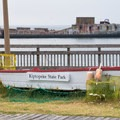 A sign with the park's name with sunken ships in the background.- Kiptopeke State Park