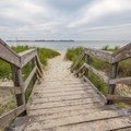 A wooden walkway crosses the dunes to the beach.- Kiptopeke State Park