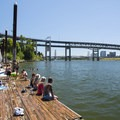 Audrey McCall Floating Dock on the Willamette River with the Marquam Bridge and Tilikum Crossing Bridge in the background.- Audrey McCall Floating Dock + Beach