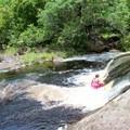 Tubing one of the falls in Lonomea.- Lonomea via the Kukui Trail