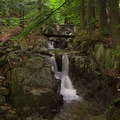 """This waterfall has been referred to as """"Footbridge Falls"""" due to the small bridge that spans the brook at one of its narrowest points.- Stag Brook Trail"""