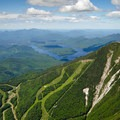 The slopes and slides of Whiteface Mountain as seen from above. Lake Placid can be seen in the background.- Stag Brook Trail