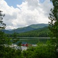 A kayaker glides by one of the trails along the lake.- Heart Lake Campground