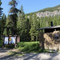 Trailhead sign and vault toilet.- Hyalite Lake