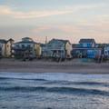 Colorful houses line the beach.- Nags Head Pier + Beach Access