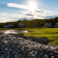 Looking over a rock wall at Cape Hedge Beach to the neighboring homes.- Cape Hedge Beach