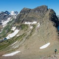 Asceding the scree field with Dragon's Back and Gunsight in the background.- Mount Reynolds Summit