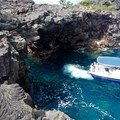 A boat venturing into the sea caves at Pu`uhonua o Hōnaunau National Historical Park.- City of Arches on Hōnaunau Bay