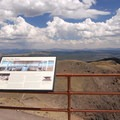 Informational sign on the second floor deck with the Absarokas in the distance.- Mount Washburn via Dunraven Pass