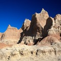 A hiker is dwarfed by the massive Badlands formations.- The Door Trail